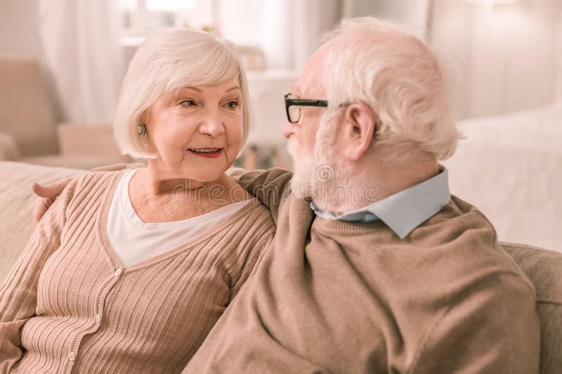 Charming grey-haired male person staring at his partner. Express tenderness. Attentive mature women listening to her husband and expressing positivity royalty free stock photo