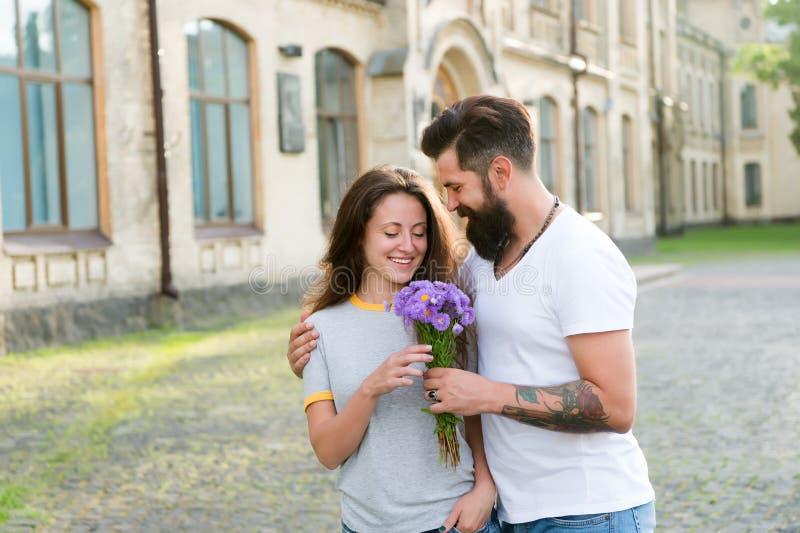 Expressando sentimentos A mulher aprecia flores do ramalhete da fragr?ncia A senhora gosta do marido da flor dotado ela Pares no  foto de stock