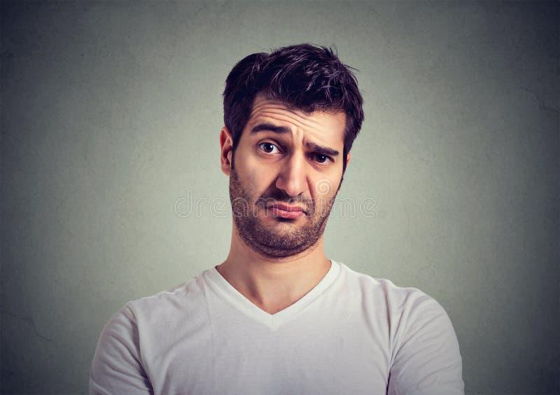 Expressar de pensamento olhando de sobrancelhas franzidas do homem novo duvida e interesses imagens de stock royalty free