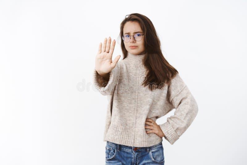 Expressar desagradado da mulher pouco disposto e para não gostar do braço de alargamento no gesto da parada que olha de sobrancel fotos de stock