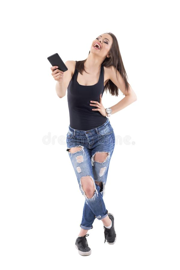 Expressieve hard lachend jonge mooie vrouw met mobiel telefoon buigend achteruit hoofd royalty-vrije stock fotografie