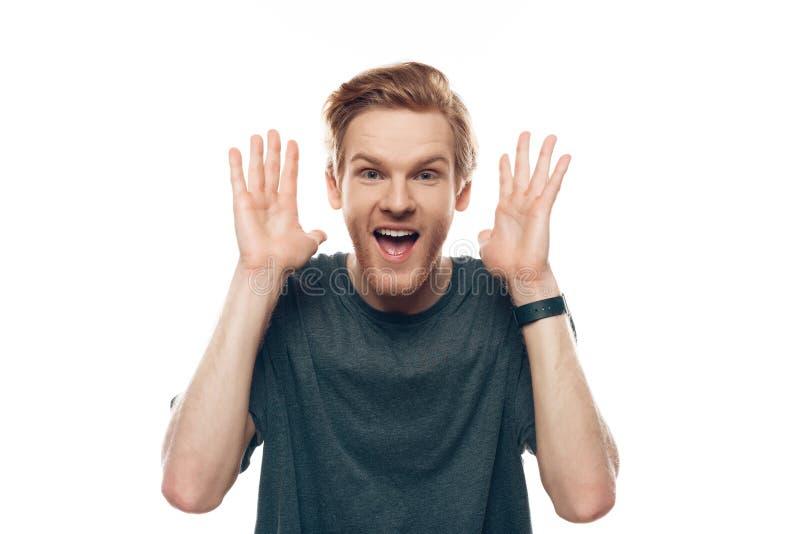 Expressieve het glimlachen jonge gebaarde mensenhanden omhoog stock afbeelding