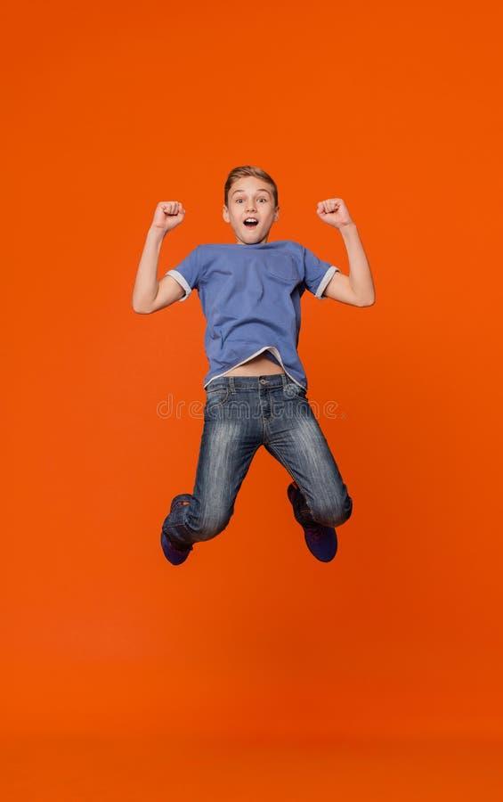 Expressieve opgewekte jongen die van succes genieten die in lucht springen royalty-vrije stock afbeelding