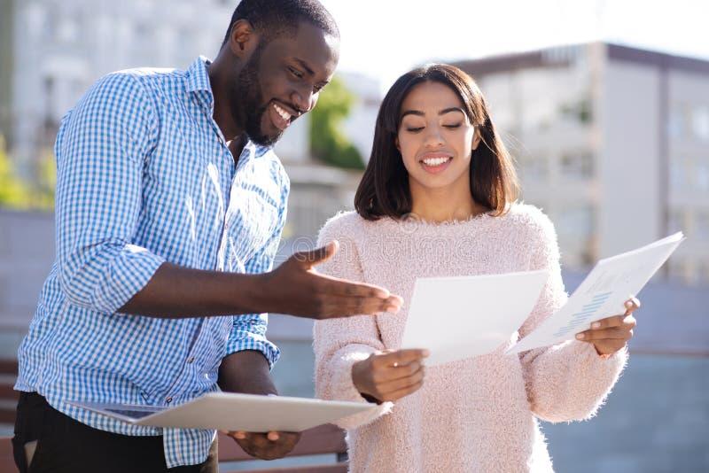 Expressieve slimme vrienden die een businessplan bespreken stock afbeeldingen