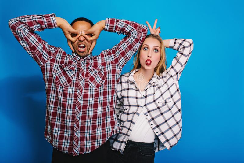 Expressing brightful positive emotions of funny excited couple having fun on blue background. Fooling around, free time. Relaxing, weekends, caper, monkey stock photos