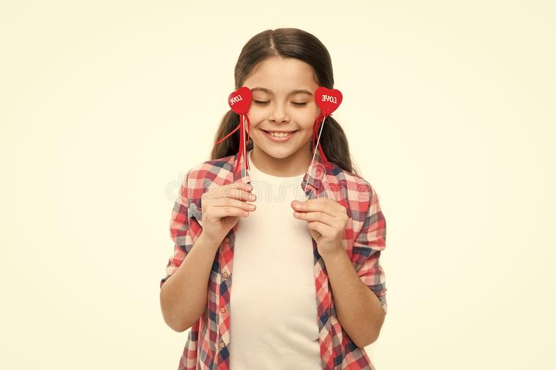Expressing the emotions of love. Small girl holding hearts on sticks. Cute girl with small red hearts. Small child with. Heart shaped decorations. Happy stock images