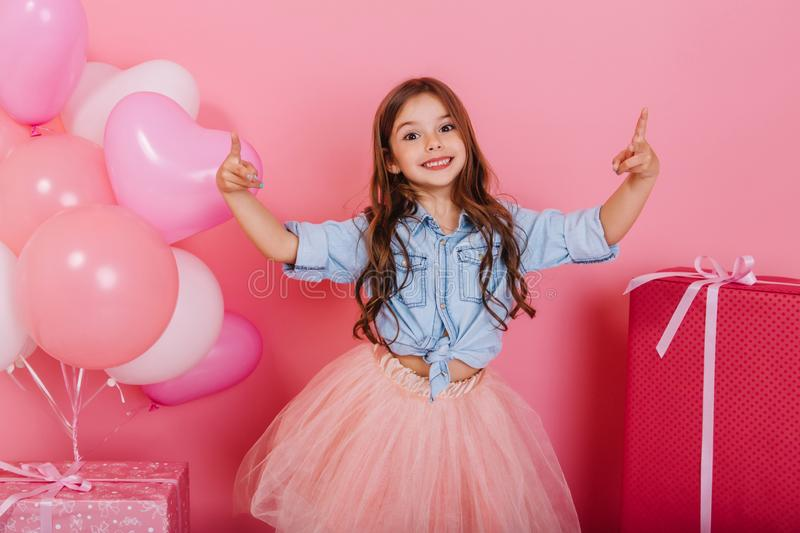 Expressing true positive emotions to camera of joyful happy kid suround balloons and presents  on pink stock image