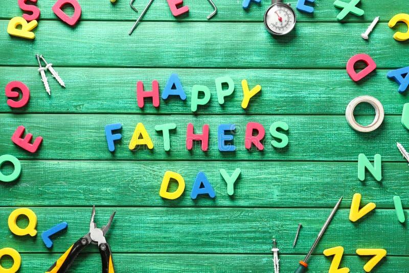 """Expression \ «père heureux \ """"jour de s \» composé de lettres et de différents outils sur le fond en bois de couleur photographie stock"""