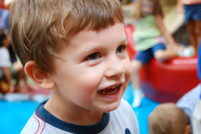 Expression. Autistic child with happy expression having fun at a play area in a mall