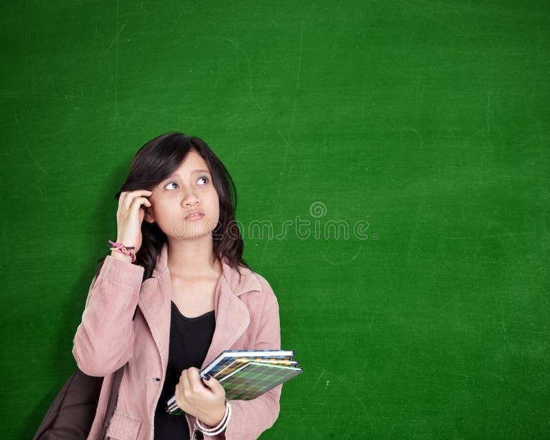 Expression confuse de fille d'école au-dessus de tableau vert images stock