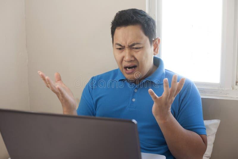 Expression d??ue d'homme f?ch? regardant l'ordinateur portable photographie stock