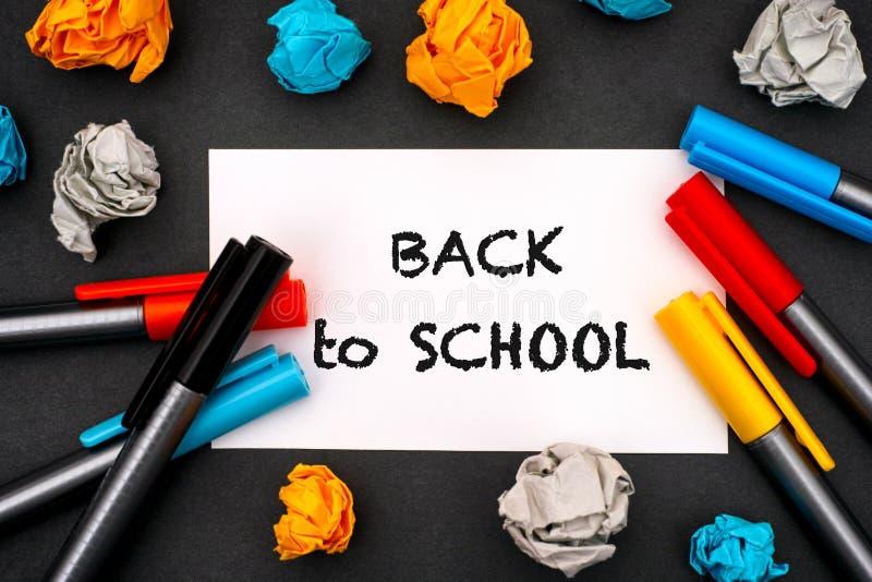 Expression de nouveau à l'école sur le blanc de livre blanc avec les stylos de couleur et le papier chiffonné image libre de droits