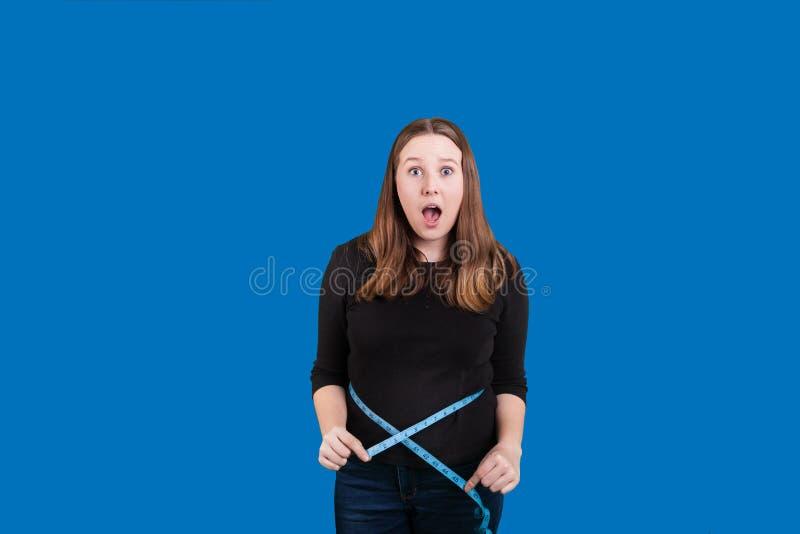 Expression de renversement sur le visage de jeunes femmes mesurant sa taille avec la mesureuse bleue de bande photos libres de droits