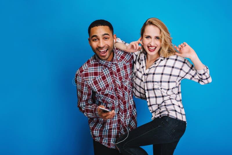 Expression des émotions positives brightful de jeunes couples heureux écoutant la musique par des écouteurs sur le fond bleu image stock