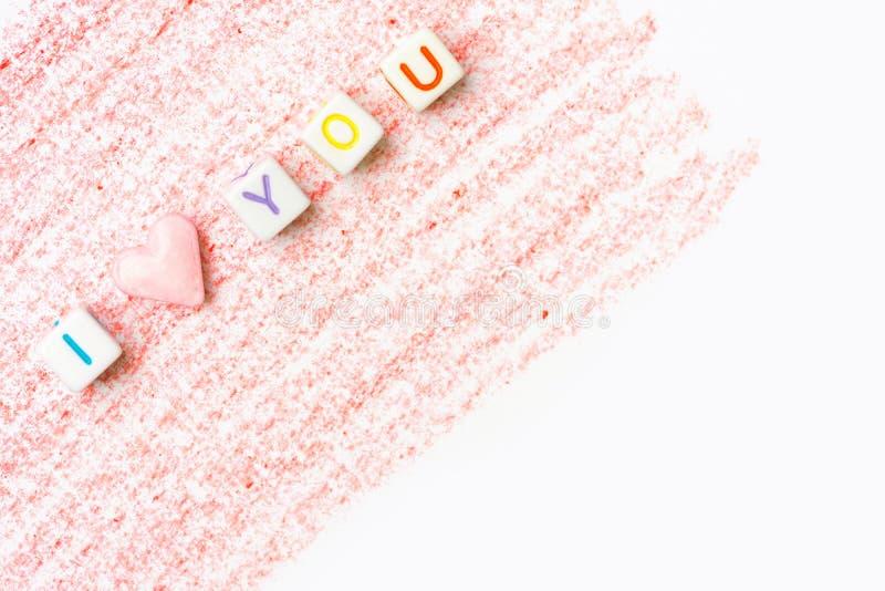 Expression je t'aime construite des cubes blancs en lettre et de la sucrerie de sucre rose de forme de coeur sur le fond rouge de photos stock