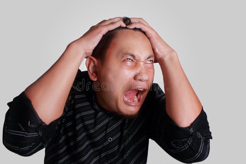 Expression soumise à une contrainte fâchée folle d'homme asiatique photo libre de droits