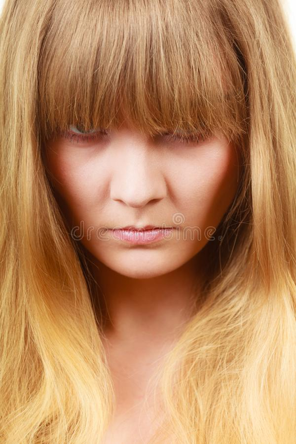 Angry looking woman, face covered in fringe. Expressions, emotions, anger, mysterious concept. Angry looking woman, face covered in her blonde fringe royalty free stock image
