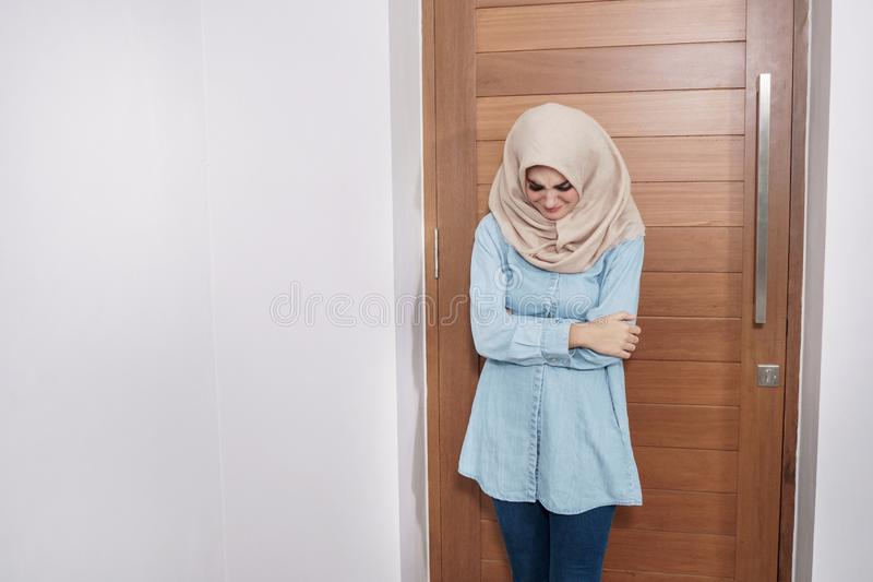 Expressions froides se sentantes de hijab de port de belle femme au foyer images libres de droits