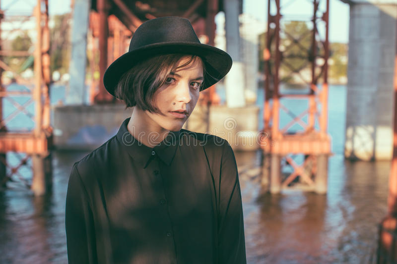 Expressive attentive look girl teenager in black hat. Beauty looking girl with stylish black hat and dress. Urban city street under bridge constructions stock photography