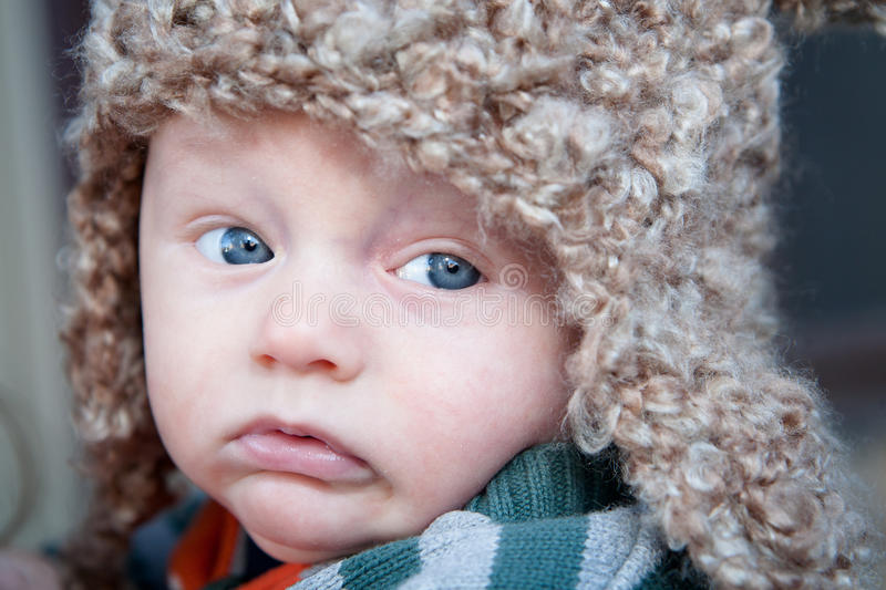 Expressive Baby. A baby boy with a dissatisfied expression on his face looking to the side with his big blue eyes royalty free stock photos