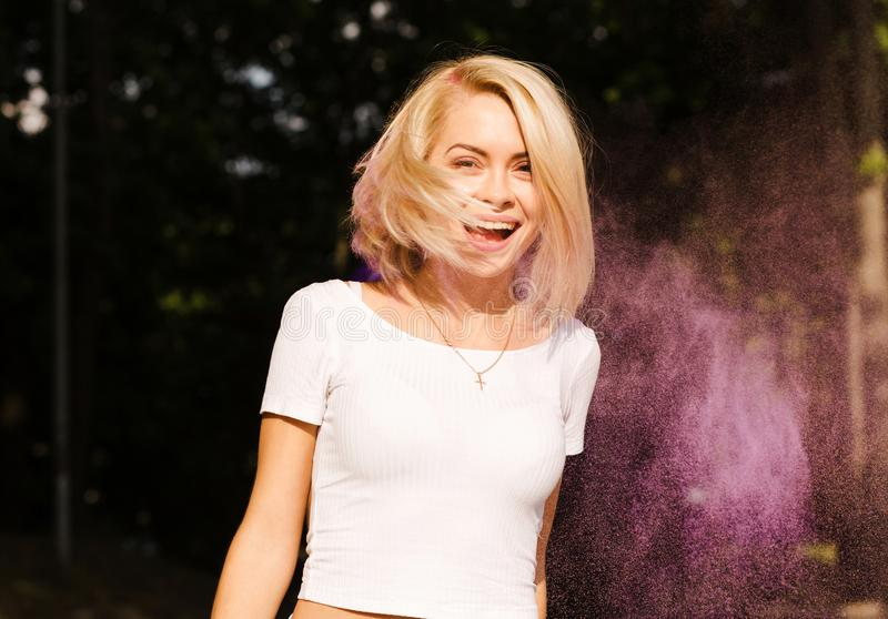 Expressive young woman in white t shirt with hair in wind posin. Expressive blonde woman in white t shirt with hair in wind posing on Holi festival royalty free stock images