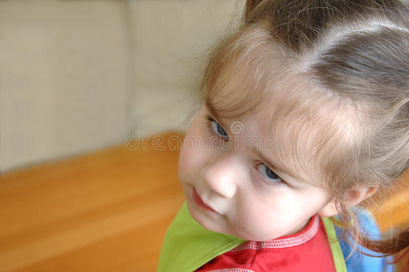 Expressive Face. Pouting little girl, looks over her shoulder and stares at camera. She is inside her home. Expression could be disbelieving, disgusted stock photography