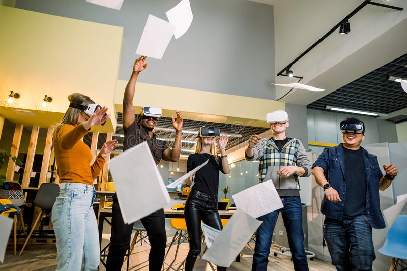 Expressive five young multiethnical people wearing virtual reality goggles watching at papers while standing in modern stock photography