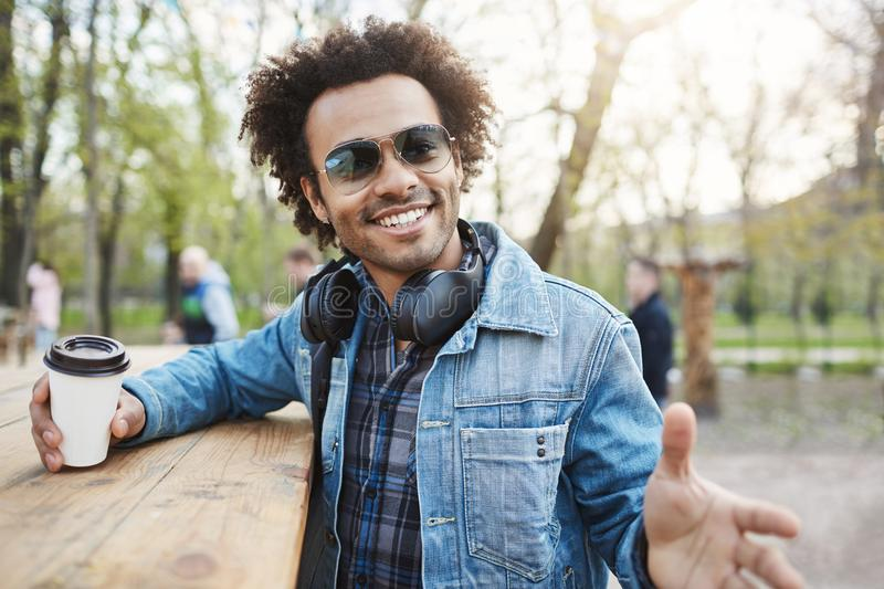 Expressive handsome dark-skinned male with afro haircut in glasses, denim coat and headphones, leaning on table while. Drinking coffee in park, gesturing as if stock photography