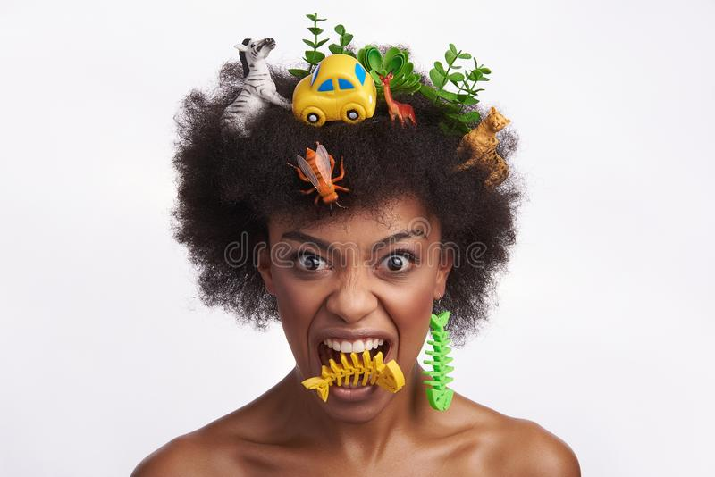 Expressive lady put fish skeleton earring in mouth royalty free stock photo