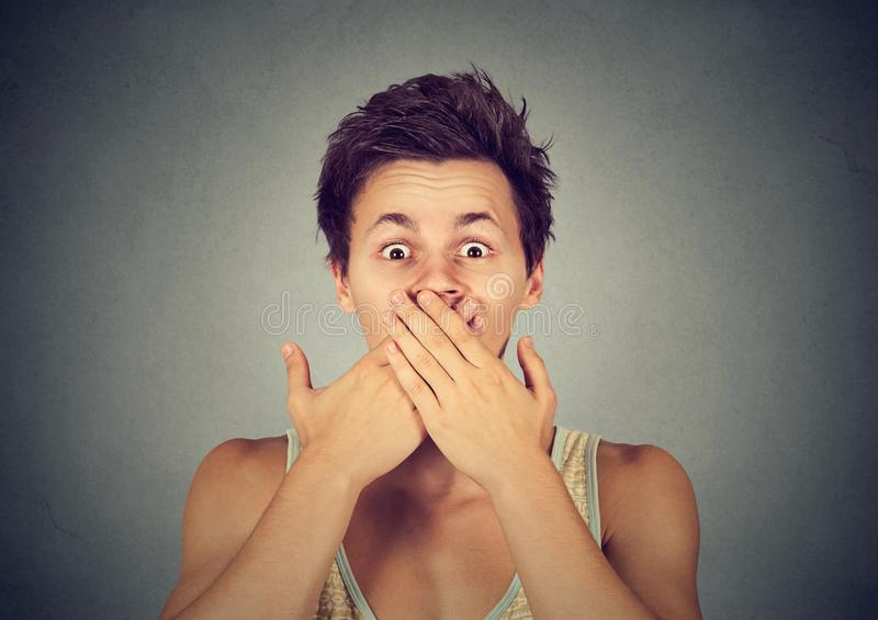Expressive man covering mouth in fear royalty free stock photography