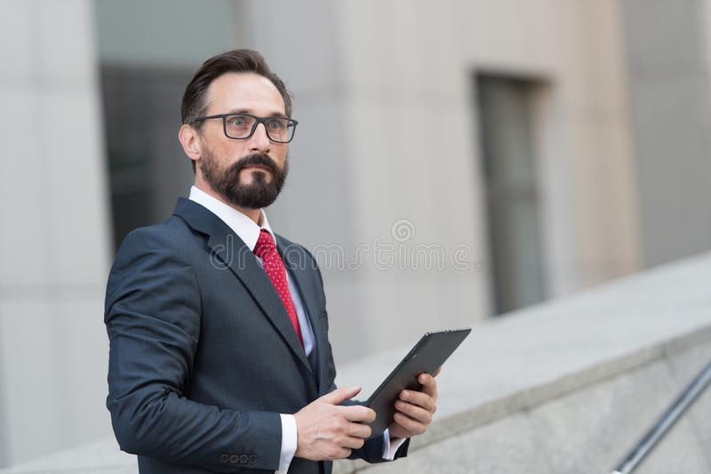 Expressive man feeling surprised while looking into the distance. Emotional elegant man in dark suit standing outdoors with modern tablet and looking surprised royalty free stock photo