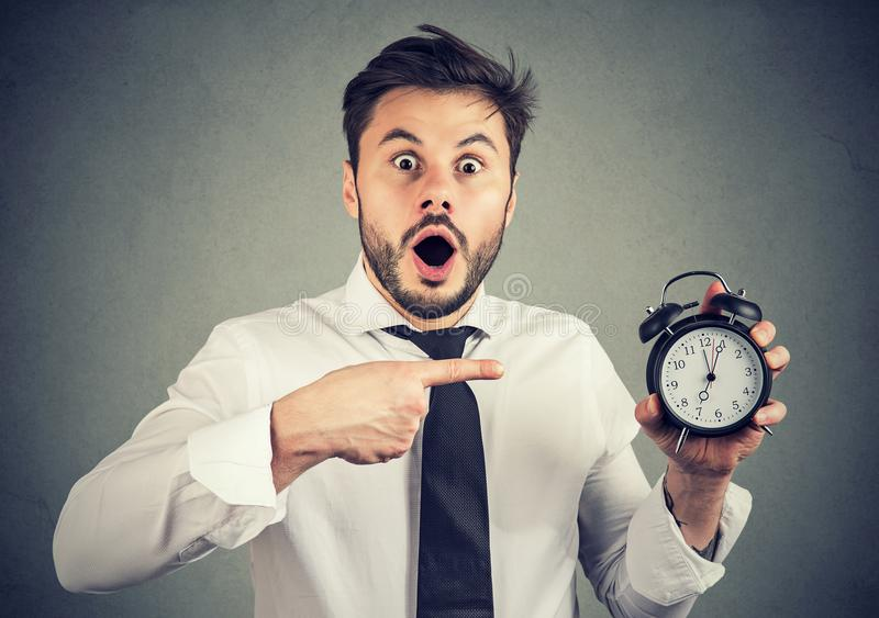 Scared man pointing at alarm clock stock images