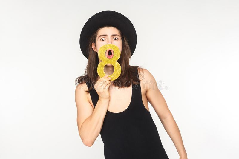 Expressive man holding number eight and shout, have a shocked lo. Expressive man holding number eight or infinity and shout, have a shocked look. Studio shot stock images