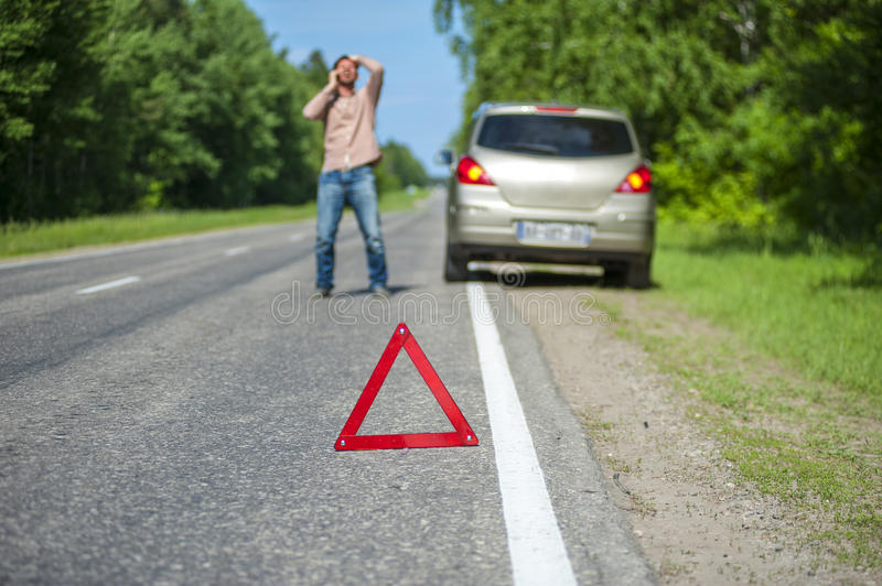 Expressive man talking on the phone after car accident. Focus on red triangle warning sign stock images