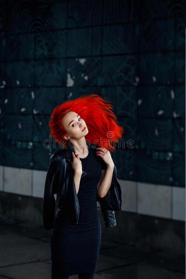 Expressive Redhead woman posing at dark wall and her hair flying against black background royalty free stock images