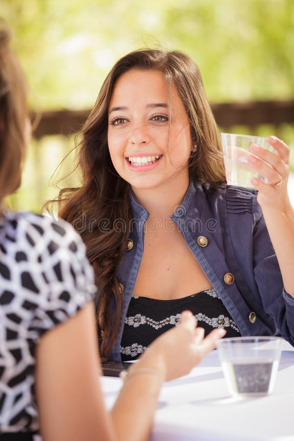 Expressive Teen Girl Having Drinks and Talking with Friend. Expressive Young Adult Woman Having Drinks and Talking with Her Friend Outdoors stock photography