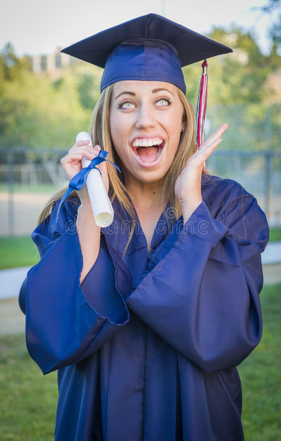 Expressive Teen Woman Holding Diploma in Cap and Gown royalty free stock image