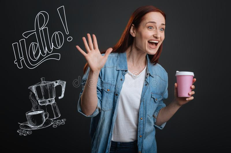 Expressive woman feeling exited while noticing her friend in a cafe. Exciting meeting. Positive emotional young woman standing with a cup of coffee and waving stock photography