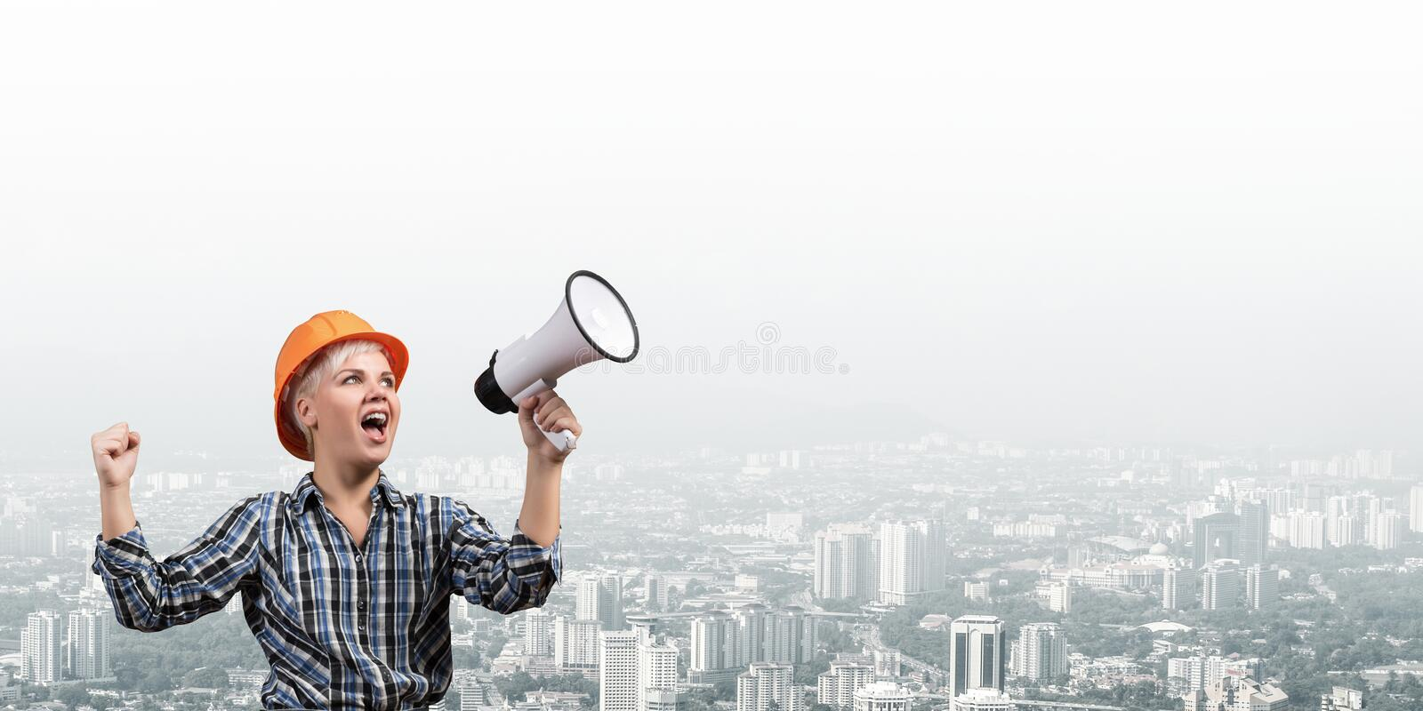 Expressive woman in helmet shouting into megaphone royalty free stock image
