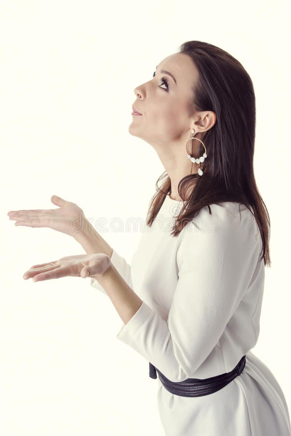 Expressive woman holding her empty hands open. Profile of young beautiful brunette woman showing empty hands with open palms. She is looking up and blowing stock photos