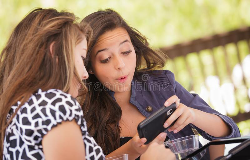 Excited Young Adult Girlfriends Using Their Smart Phone. Expressive Young Adult Girlfriends Using Their Computer Electronics Outdoors royalty free stock photos