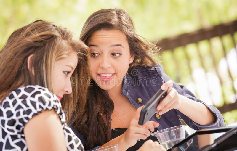 Expressive Young Adult Girlfriends Using Their Smartphone. Expressive Young Adult Girlfriends Using Their Computer Electronics Outdoors stock photo