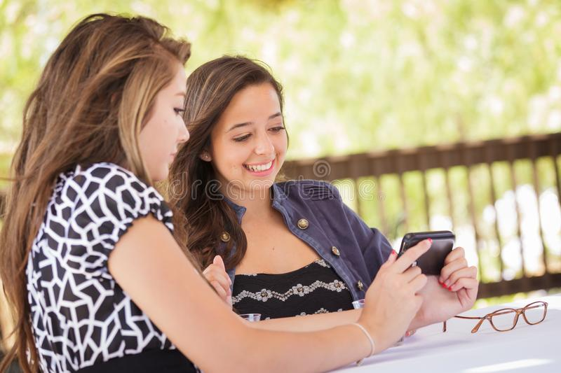 Pretty Young Teen Girlfriends Using Their Smart Phone. Expressive Young Adult Girlfriends Using Their Smart Cell Phone Outdoors royalty free stock photo