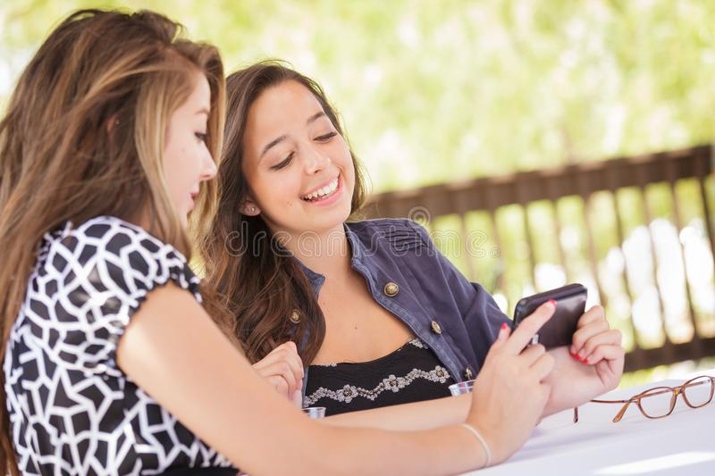 Two Young Adult Girlfriends Using Their Smart Cell Phone. Expressive Young Adult Girlfriends Using Their Smart Cell Phone Outdoors royalty free stock photo