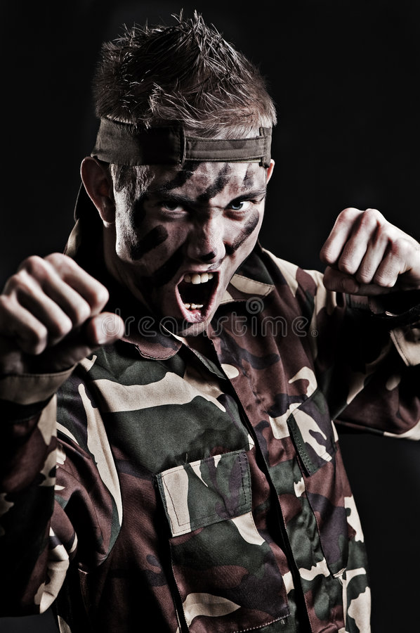 Expressive young soldier. Over black background stock image