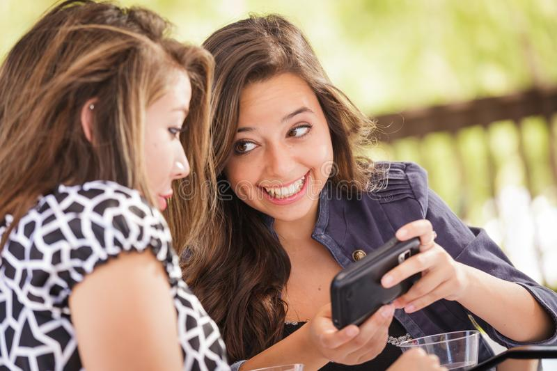 Expressive Young Teen Girlfriends Using Smart Phones. Expressive Young Adult Girlfriends Using Their Computer Electronics Outdoors stock photography