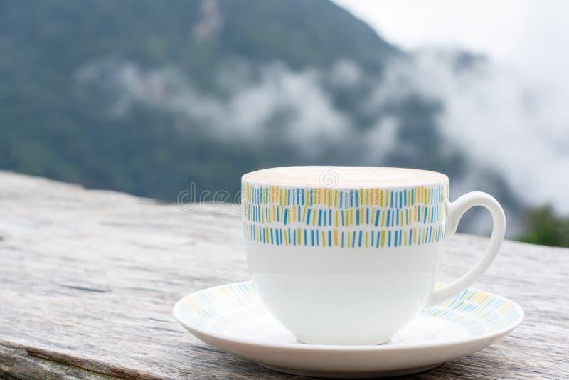 Expresso chaud, cappuccino, latte dans la tasse blanche en céramique sur la table en bois avec la montagne trouble et nuage de ca photographie stock libre de droits