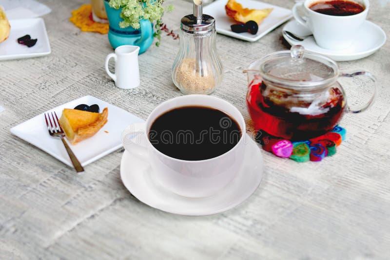 Expresso de café dans la tasse blanche et thé dans le pot avec la tarte aux pommes sur a images stock
