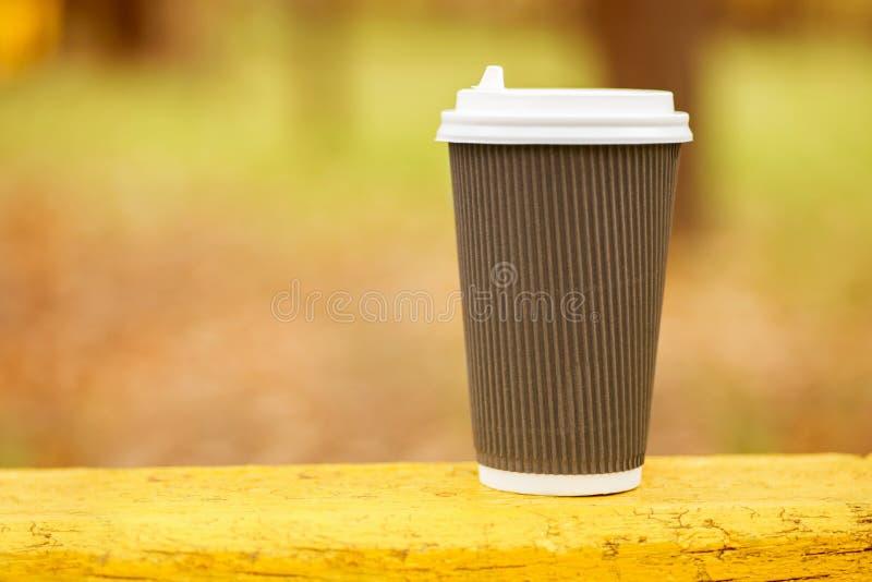 Expresso de café sur le fond en bois de nature de table en parc, ton chaud Tasse de café jetable sur le fond jaune image libre de droits