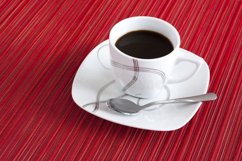 Expresso med skeden på röd bordduk arkivbild